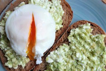 gepocheerd ei op een boterham met avocado-cottagecheese