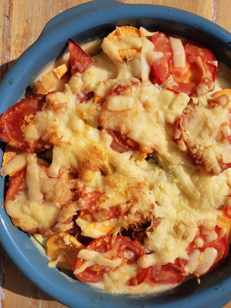Clafoutis in een ovenschaal met tomaat, courgette, chorizo en zoete aardappel